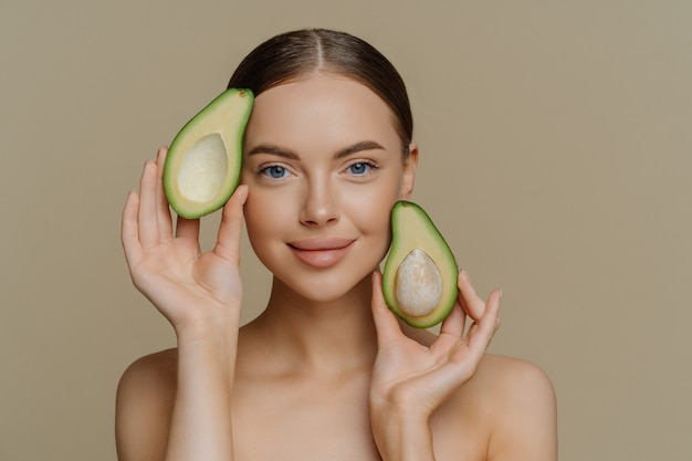 Photo of shirtless female model looks with gentle expression, holds halves of avocado near face has healthy well cared skin after cosmetic treatments