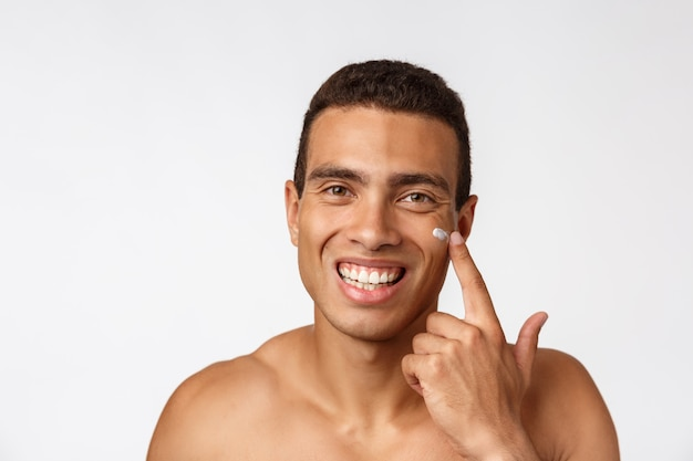 Photo of shirtless man smiling and applying face cream isolated over white