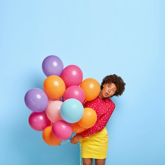 Photo of shocked african american woman looks with omg expression, holds many colorful helium airballoons, dressed in vivid shirt and skirt