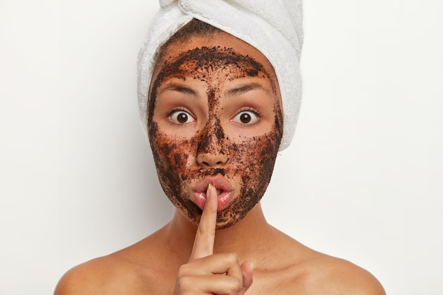 Photo of shocked afro american woman with coffee scrub for peeling from pores, makes silence gesture, has surprised face expression, shows bare shoulders, tells secret, has cosmetology procedure