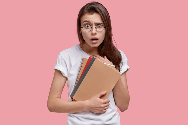 La foto della donna attraente scioccata ha un'espressione sorpresa, trasporta il blocco note a spirale, i libri di testo, vestita con una maglietta casual bianca