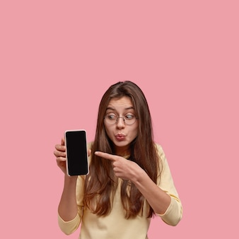Photo of shocked brunette lady keeps lips folded, indicates with index finger at mock up screen of cellular, demonstrates something astonishing