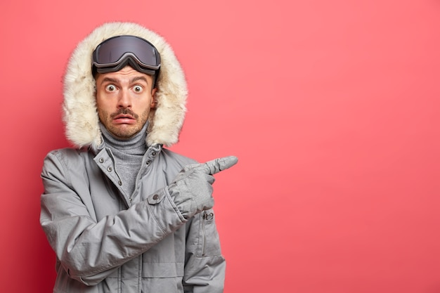 Photo of shocked emotional european man dressed in winter clothes wears ski goggles and points away on blank space gives direction on right.