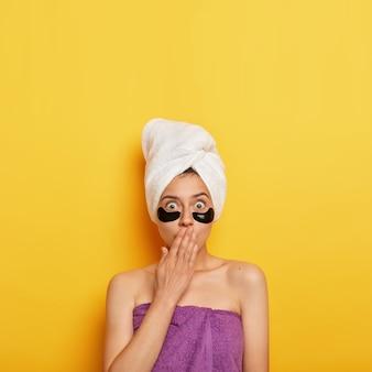 La foto di una donna europea scioccata copre la bocca con il palmo della mano, applica cerotti sotto gli occhi per rimuovere le rughe, fa il bagno regolarmente, vuole avere una pelle perfetta