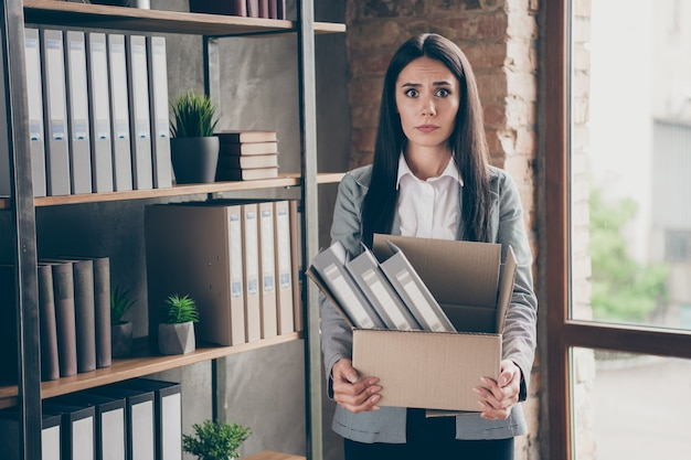 Photo of shocked frustrated girl lawyer representative lose her job dont know how live coronavirus crisis hold cardboard box wear blazer jacket suit in workplace workstation
