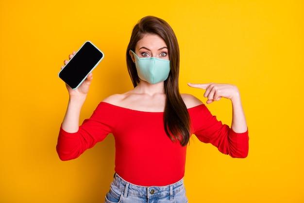 呼吸マスクポイント人差し指スマートフォンで写真ショックを受けた女の子は、新しいデバイスをお勧めしますcovid検疫ソリューションは、赤いトップデニムジーンズを着用し、明るい輝きの色の背景を分離しました