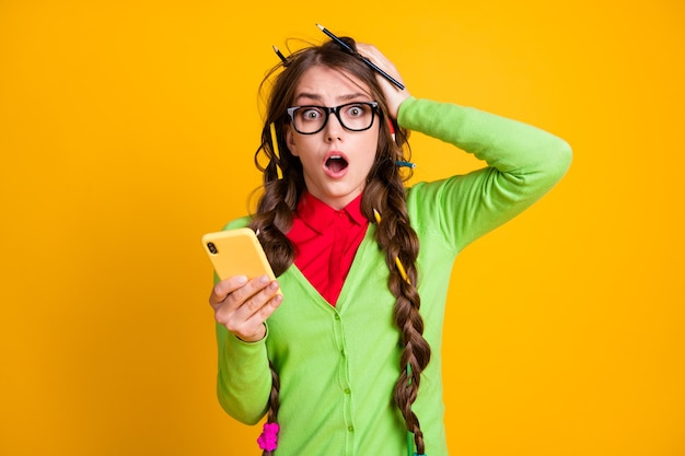 Photo of shocked girl messy hairdo hold smartphone shout isolated shine color background