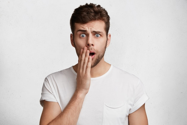 Photo of shocked handsome man with attractive look, stares at camera in bewilderment, hears bad news, poses in studio against white background. people, facial expressions and unexpectedness concept
