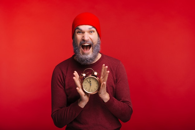 Photo of shocked man with white beard holding alarm clock