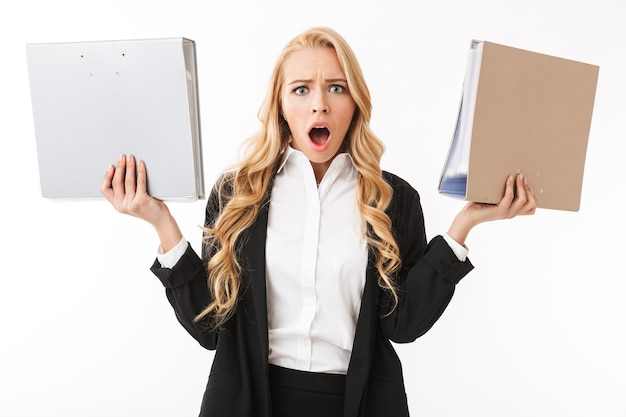 Photo of shocked manager girl wearing office suit holding paper folders in hands, isolated