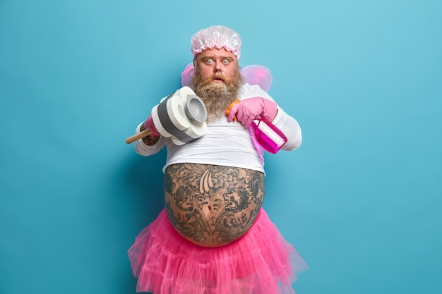Photo of shocked plump bearded man pretends being fairy of purity cleans something holds bottle of detergent and plunger has big tattooed belly
