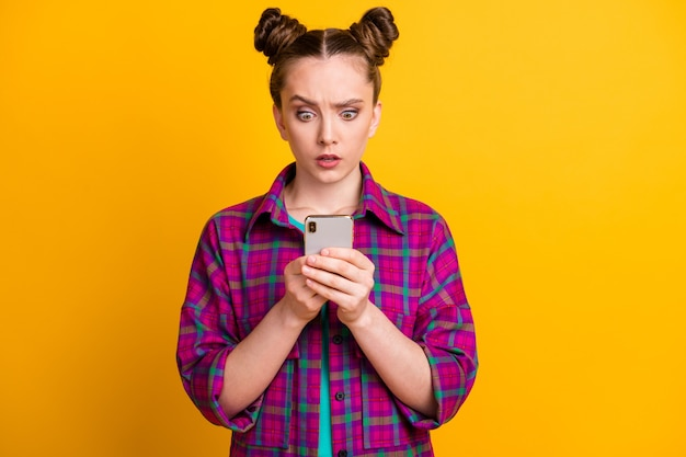 Photo of shocked teen lady two buns look telephone read comments blog quarantine bad news speechless stupor wear casual checkered shirt isolated yellow bright color background