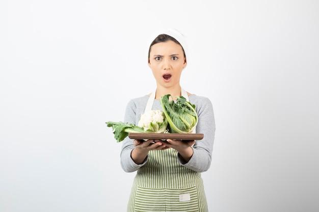 Foto di una donna scioccata in grembiule con in mano un piatto di legno con cavolfiori