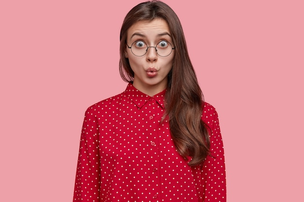 Photo of shocked woman in stupor, keeps lips round, has distrubing situation, dressed in fashionable polka dot blouse, wears round spectacles