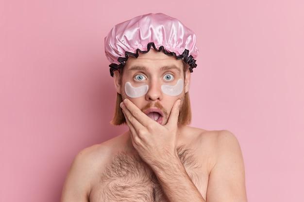 La foto del giovane uomo caucasico scioccato tiene gli sguardi del mento con gli occhi saltati fuori applica cuscinetti di collagene sotto gli occhi