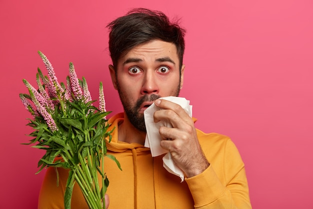 Photo of shocked young man allergic to spring flowers or plants, has asthmatic disease, redness around nose, holds hankechief, isolated on pink wall. health care, hay fever, sickness concept