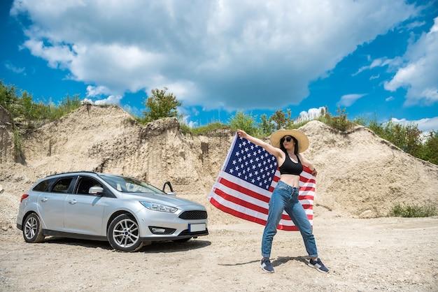여름에 모래 채석장에서 차 근처에 미국 국기가 달린 매력적인 여성의 사진 촬영