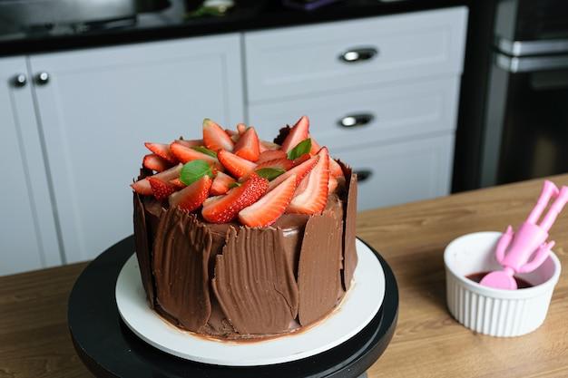 Фотосессия с украшением шоколадного торта. шоколадный торт, покрытый клубникой, свежими листьями базилика, ежевичным вареньем и шоколадными тарелками.