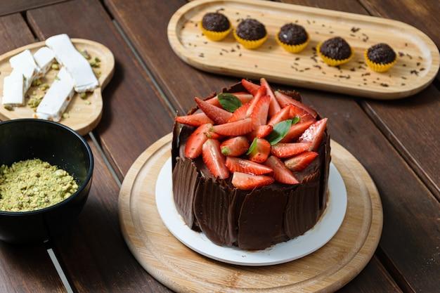 チョコレートケーキを飾った写真撮影。イチゴ、新鮮なバジルの葉、ブラックベリージャム、チョコレートプレートで覆われたチョコレートケーキ。