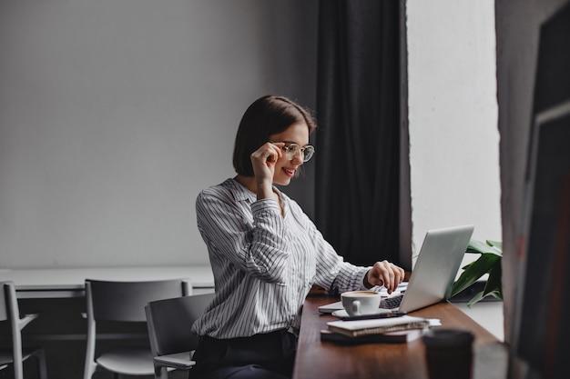 Foto di donna d'affari dai capelli corti in bicchieri e camicetta bianca seduto sul posto di lavoro e lavora nel computer portatile.