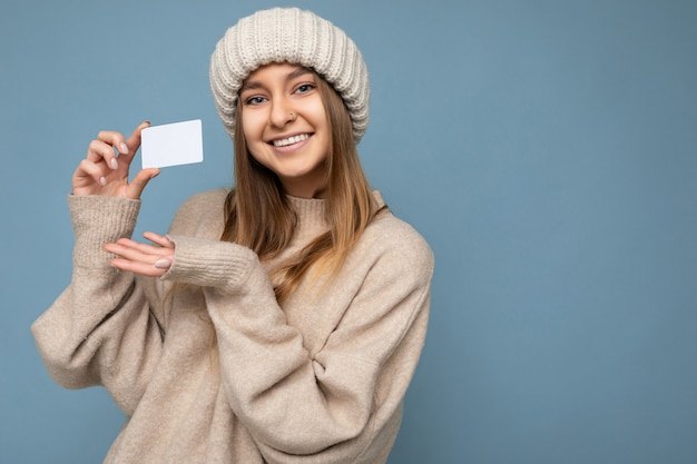 Photo shot of attractive positive smiling young dark blonde woman wearing beige sweater and knitted