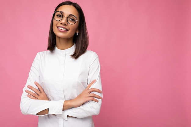 Photo shot of beautiful positive smiling young brunette woman wearing casual clothes and stylish optical glasses isolated over colorful background looking at camera. empty space