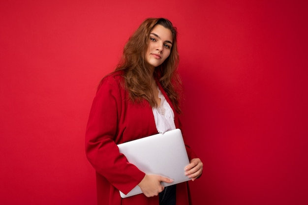 Photo shot of beautiful smiling happy young brunet female person holding computer laptop wearing red cardigan and white shirt looking at camera isolated over red wall background.