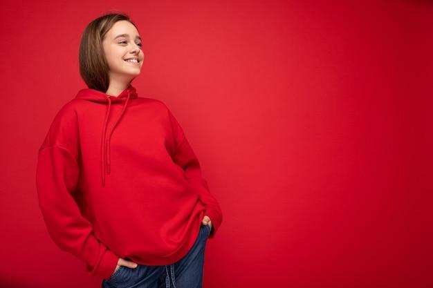 横を向いている赤い背景の壁の上に孤立して立っているスタイリッシュな赤いパーカーを着ている魅力的な幸せなポジティブな笑顔のブルネットの女性のティーンエイジャーの写真撮影。空のスペース、コピースペース