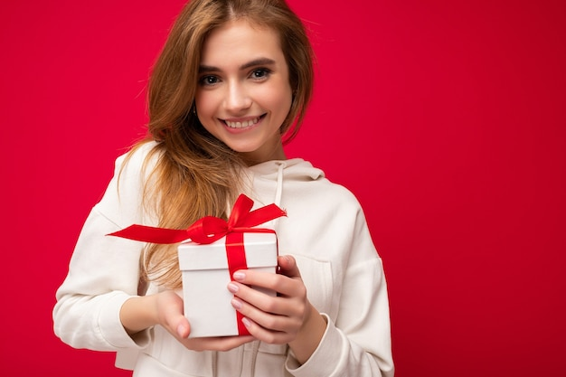 赤いリボンと白いギフトボックスを保持し、カメラを見ている白いパーカーを着て赤い背景の壁に隔離された魅力的な幸せな笑顔のかわいい金髪の若い女性の写真のショット。フリースペース
