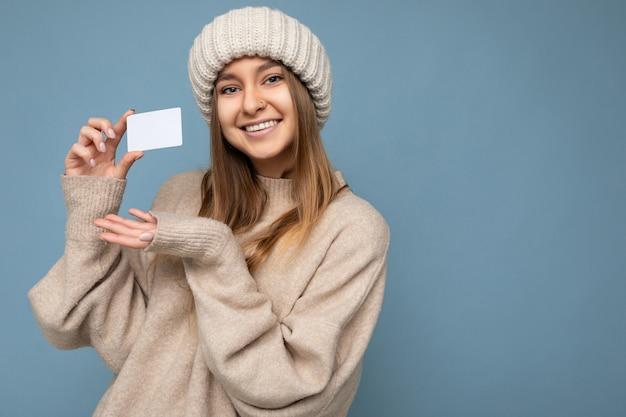 베이지색 스웨터와 니트를 입고 매력적인 긍정적인 웃는 젊은 어두운 금발 여자의 사진 샷