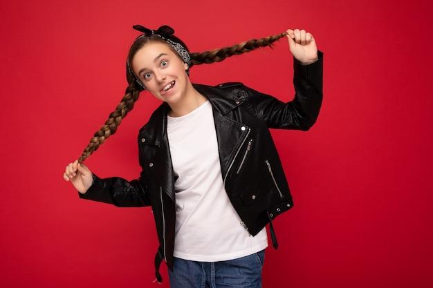 Фотоснимок красивой счастливой улыбающейся маленькой девочки-брюнетки с косичками в модной черной кожаной куртке и белой футболке для макета, стоящей изолированно над красной фоновой стеной и смотрящей в камеру