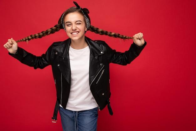 トレンディな黒い革のジャケットとモックアップの白いtシャツを身に着けているおさげ髪の美しい幸せな笑顔のブルネットの少女の写真は、カメラを見て赤い背景の壁の上に孤立して立っています。