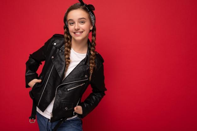 Фотоснимок красивой счастливой улыбающейся маленькой девочки-брюнетки с косичками в модной черной кожаной куртке и белой футболке, стоящей изолированно над красной фоновой стеной и смотрящей в камеру