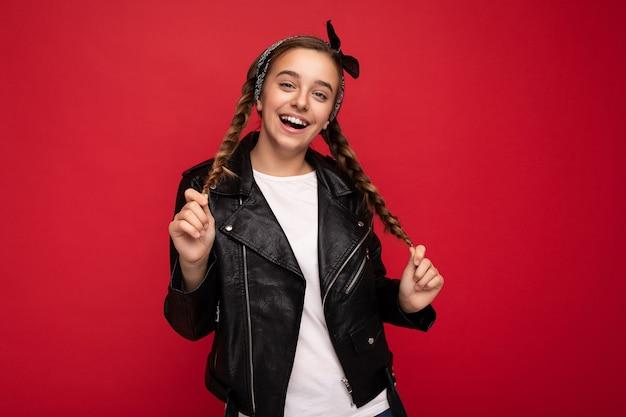 トレンディな黒い革のジャケットと白いtシャツを身に着けているおさげ髪の美しい幸せな笑顔のブルネットの少女の写真撮影