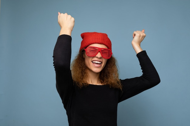 カジュアルな服を着て美しい幸せな笑顔の若い暗いブロンドの女性の写真撮影赤いバンダナと