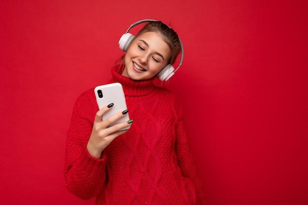 分離されたスタイリッシュなカジュアルな服を着て美しいうれしそうな笑顔の若い女性の写真撮影