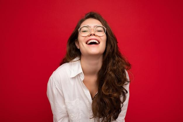 Фотоснимок красивой позитивной молодой брюнетки в повседневной одежде и стильных оптических очках