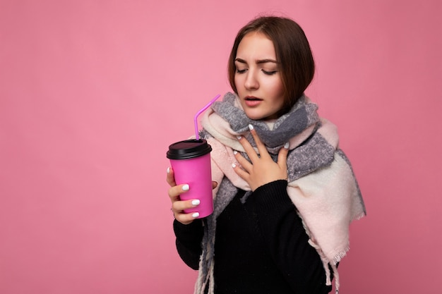 Фотоснимок красивой грустной молодой брюнетки в черном свитере и теплом шарфе на розовом фоне, держащей бумажную кофейную чашку для макета, пьющей горячий напиток и качающей