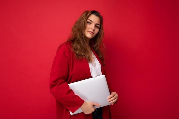 Снимок фотографии красивых улыбающихся счастливых молодых брюнеток женского пола, держащего компьютерный ноутбук в красном кардигане и белой рубашке, глядя на камеру, изолированные на фоне красной стены.
