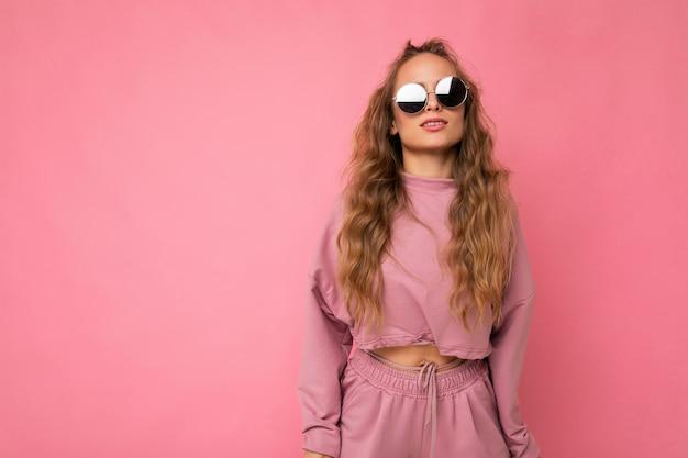 캐주얼 옷과 세련된 선글라스를 착용하고 아름다운 젊은 어두운 금발의 여자의 사진 촬영