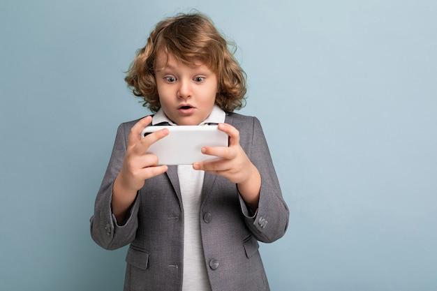 Фотоснимок красивого изумленного эмоционального ребенка-мальчика с вьющимися волосами в сером костюме, держащего и