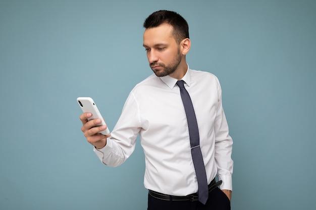 Фотоснимок красивого сконцентрированного симпатичного молодого бизнесмена в повседневной одежде