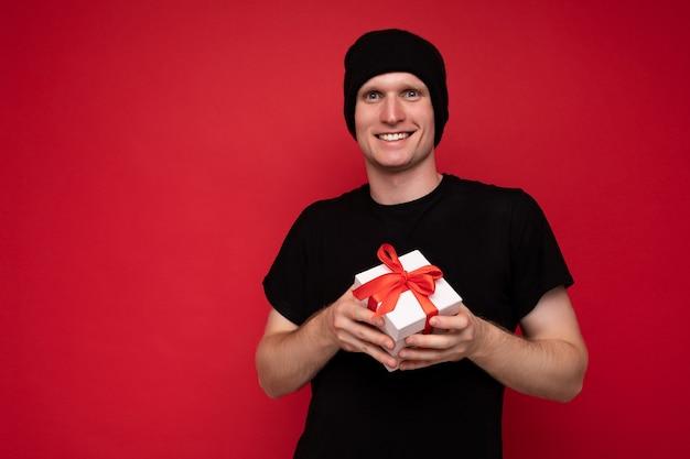 블랙을 입고 빨간 벽 위에 절연 잘 생긴 긍정적 인 웃는 젊은 남자의 사진 촬영