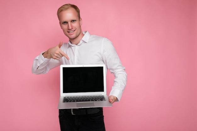 Фотоснимок красивого улыбающегося блондинки, держащего компьютерный ноутбук с пустым экраном монитора с