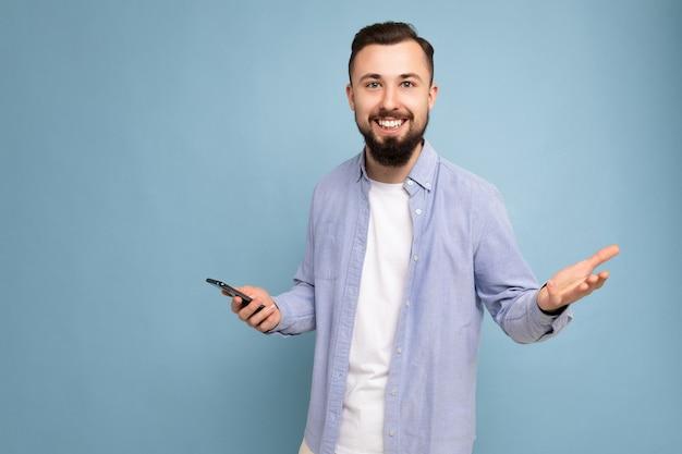 カジュアルでスタイリッシュな服を着ているハンサムな笑顔のポジティブな格好良い若い男の写真撮影