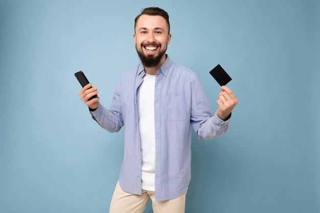 Снимок позитивного красивого бородатого симпатичного молодого человека в повседневной стильной одежде