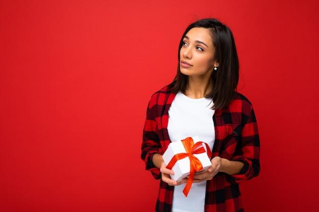 흰색을 입고 빨간색 배경 벽 위에 절연 긍정적 인 젊은 여자의 사진 촬영