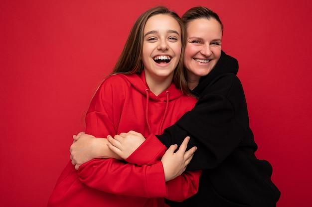 スタイリッシュな赤いパーカーと大人を身に着けているかなりポジティブな笑顔のブルネットの女性のティーンエイジャーの写真撮影