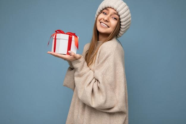 スタイリッシュなセーターと赤いリボンと白いギフトボックスを保持している冬の帽子を身に着けている青い壁の壁に隔離されたセクシーな魅力的な幸せな笑顔のダークブロンドの若い女性の写真撮影。