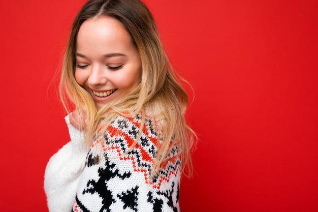 赤で隔離の冬のセーターを着ている若い美しいかわいい幸せなブロンドの女性の写真撮影